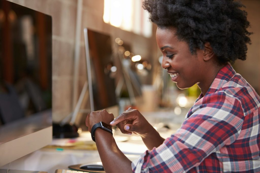 Woman using wearable smart watch at desk