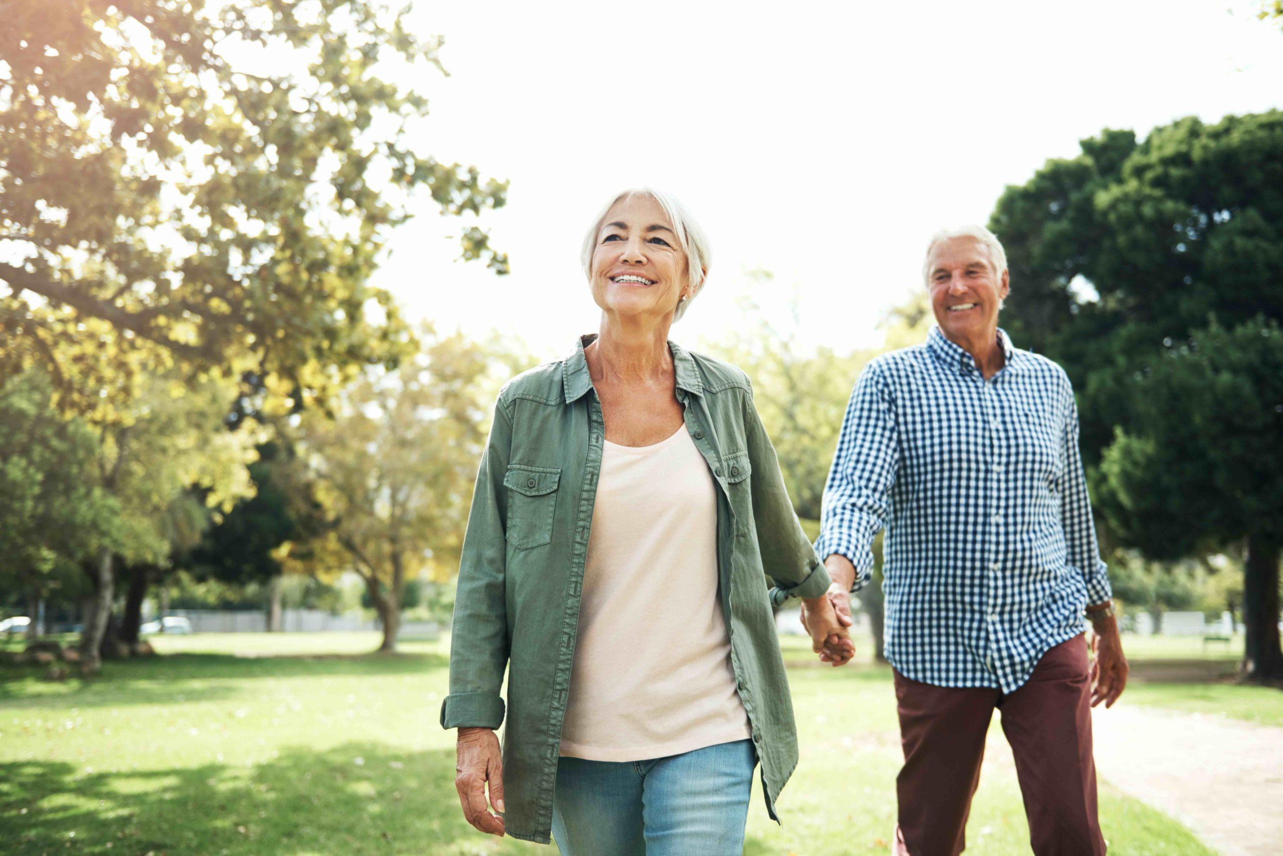 Happy senior couple enjoying walk in the park