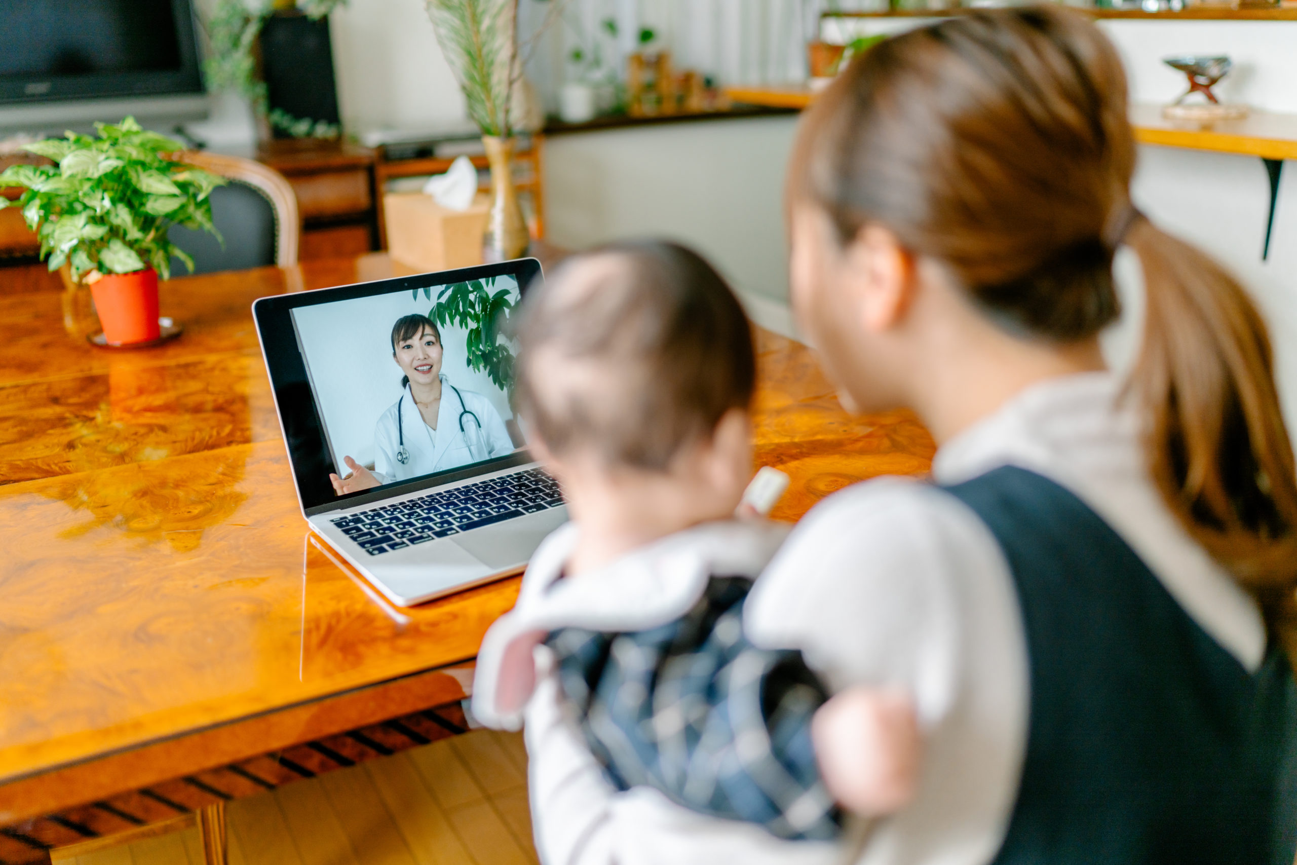 Mother with her baby video calling doctor from home