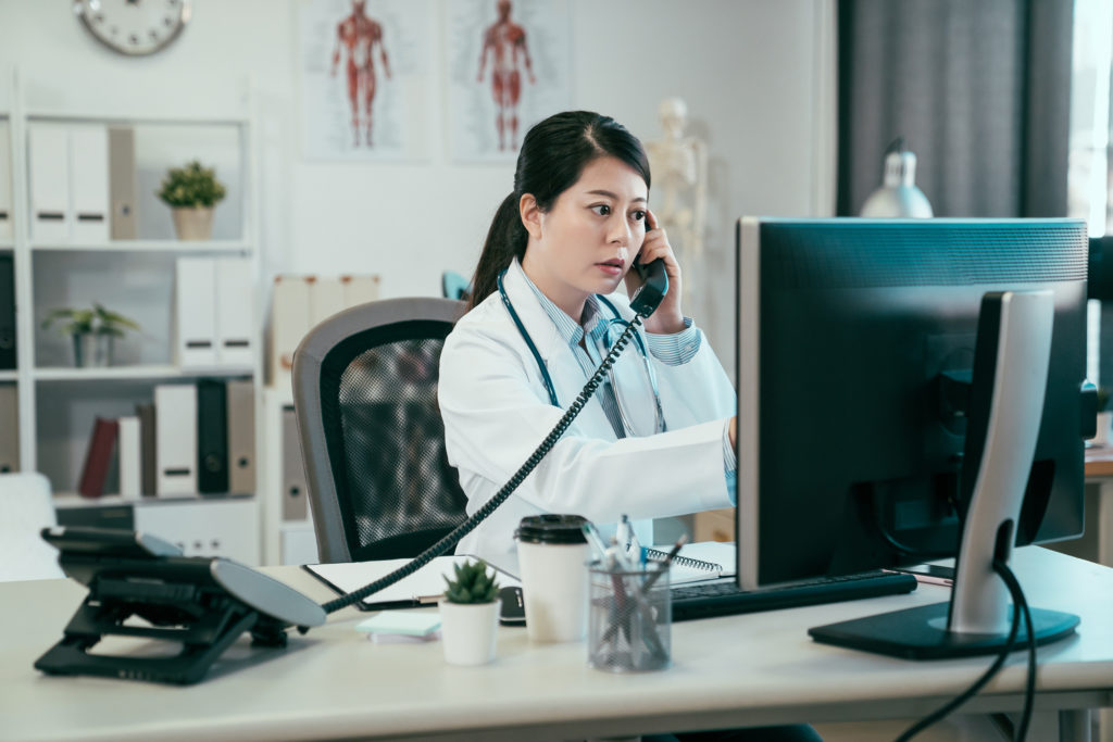 Doctor making phone call to ask question.