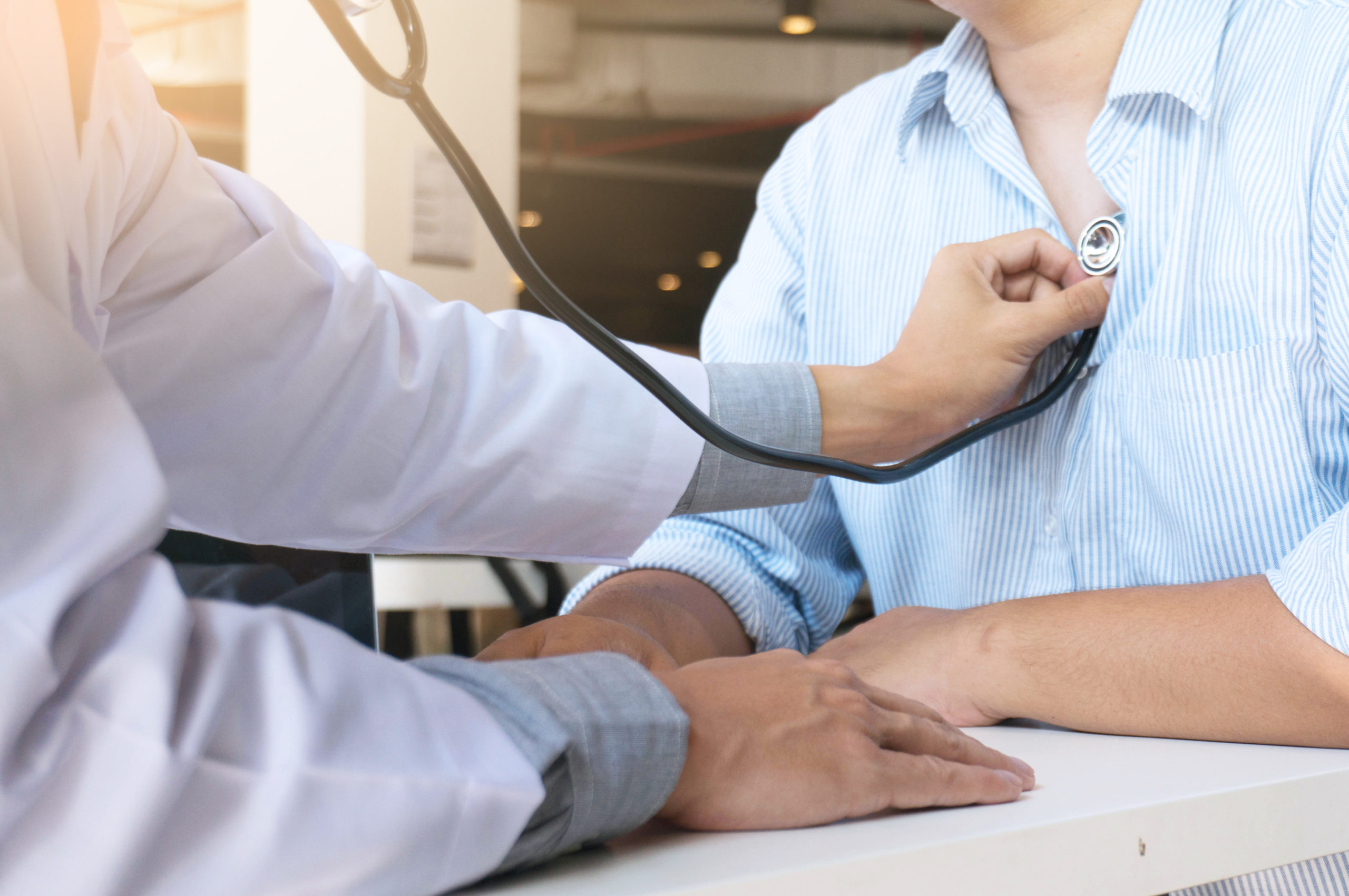 Provider checks patient's heartbeat using stethoscope.